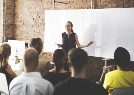 Woman giving a business training in front of a group of people